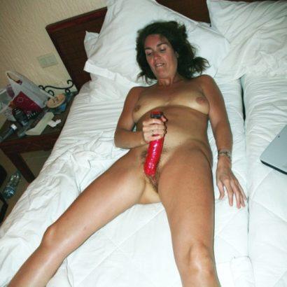 Frau mastrubiert auf dem Bett
