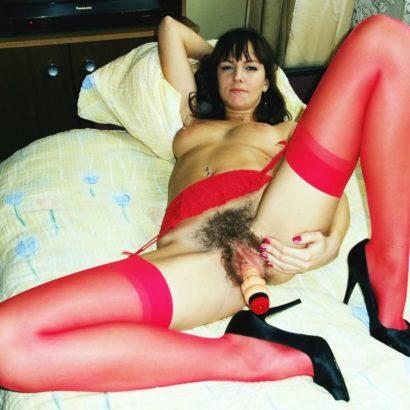 Frau mastrubiert in roten Strapsen